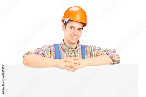 Satisfied male construction worker standing behind panel