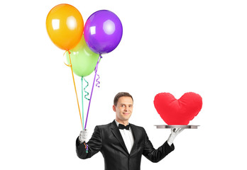 A butler holding balloons and a tray with a heart shape object