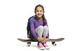 8 year old school girl with backpack sitting on a skateboard on