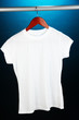White t-shirt on hanger on blue background