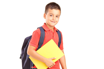 A school boy with backpack holding a notebook