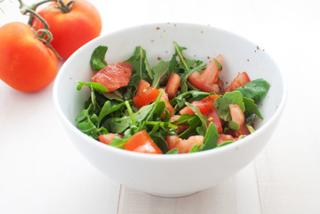 Salad with tomatoes and arugula under balsamic vinaigrette