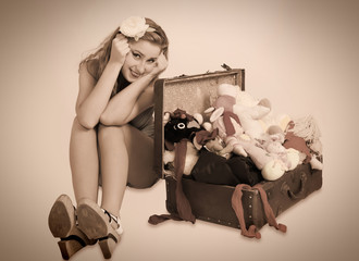 Pretty pin up woman sitting near her suitcase, toned in vintage