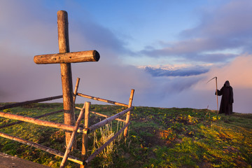 Catholic cross on a mountaintop and death that stands apart