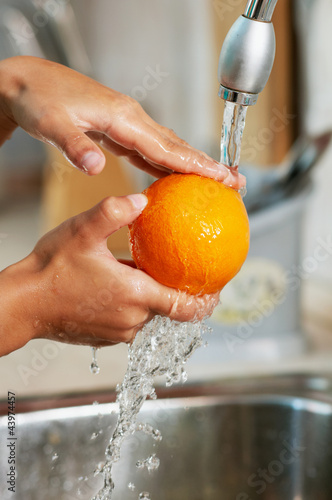 The orange is being washing  in the water