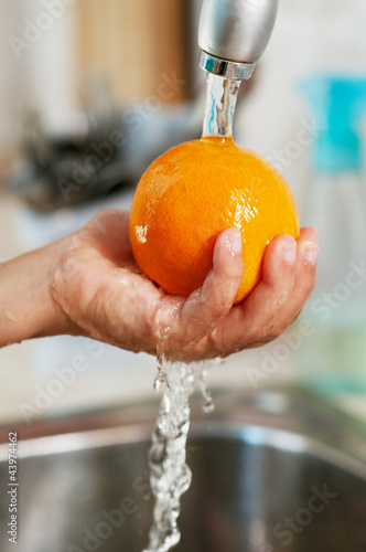 The orange is being washed in the water