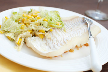 White fish fillet with salad and wine in restaurant
