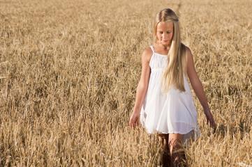 Mädchen spaziert nachdenklich im Getreidefeld