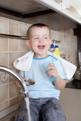 funny little child boy washing dish on kitchen