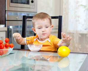cute little boy eating healthy food at kitchen