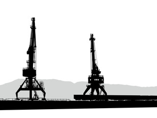 Silhouettes of two port cranes in port