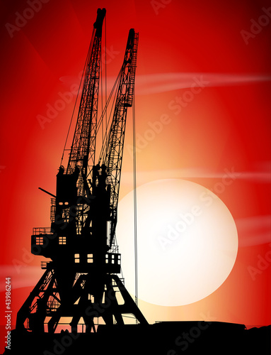 Silhouettes of two port cranes on a sunset