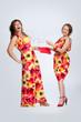 Two beautiful fashionable women in multicoloured dresses. Studio