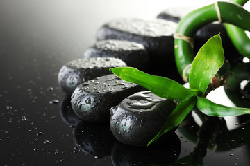 Spa stones with drops and green bamboo on grey background