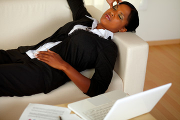 Young woman lying with eyes closed and headache