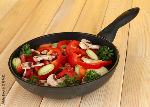 frying pan with vegetables on wooden background