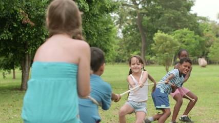 Happy school children playing tug of war in park