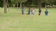Boys and girls playing football in park. Slow motion
