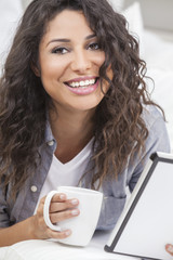 Woman Smiling Drinking Tea or Coffee Using Tablet Computer
