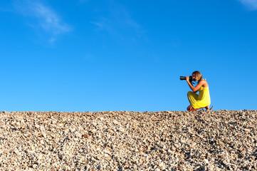 Junge Frau in gelbem Kleid beim Fotografieren
