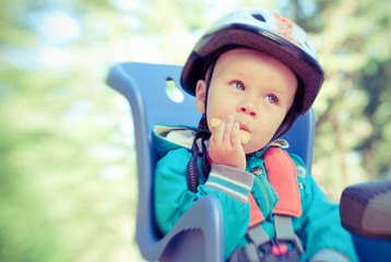 Little boy in bike child seat eating cracker. Cross process