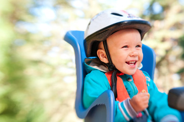 Little boy in bike child seat happy laughing