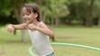 Happy little girl playing hula hoop in park. Slow motion