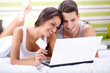Smiling couple shopping online while lying on their bed
