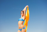 happy woman with yellow sarong on the beach
