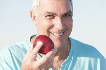 Mature man holding an apple