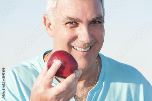 Mature man holding an apple