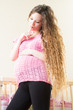 Pregnant woman with long hair near crib