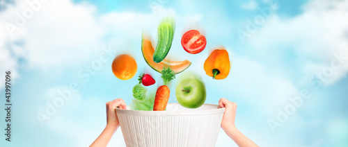 Hands are holding basket against sky background, vegetables, fru
