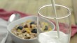 Pouring Milk in a glass (with Muesli in the background)