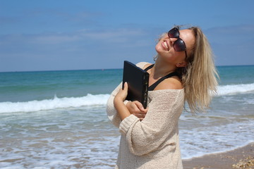 Beautiful blonde at the beach with laptop