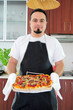 Young man in kitchen with homemade pizza
