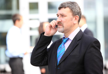 A handsome business man on phone at office building