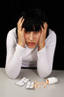 Women with headache holds her head, with lots of pills in front