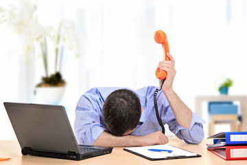 Exhausted businessman holding a telephone in his office
