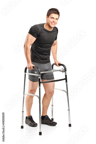 Full length portrait of a young smiling athlete using a walker