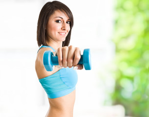 Gorgeous woman lifting a dumbbell