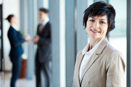 middle aged businesswoman in office with colleagues