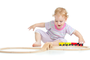 happy cute child playing with toy railroad isolated on white