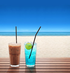 ice coffee with blue soda with lime on the summer beach