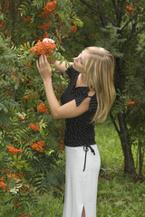Pretty model posing in outdoor admiring ashberry tree