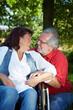 Seniorin im Rollstuhl neben Partner