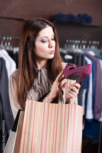 Woman attentively looks at excellent fuchsia shoes at the shop