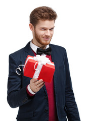 Man in bow tie offers a present wrapped in red gift paper