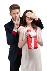 Making silence gesture man closes eyes of his girlfriend