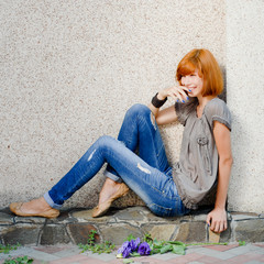 Young beautiful woman sitting near wall and laughing happilly